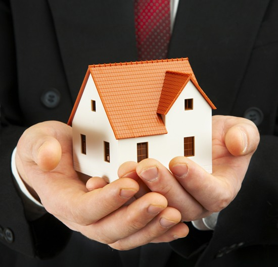 businessman holding small model house in his hands