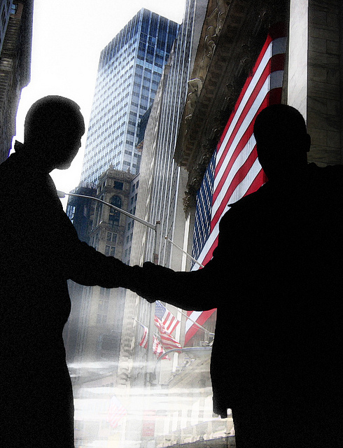Silhouetted men shake hands in front of American flag