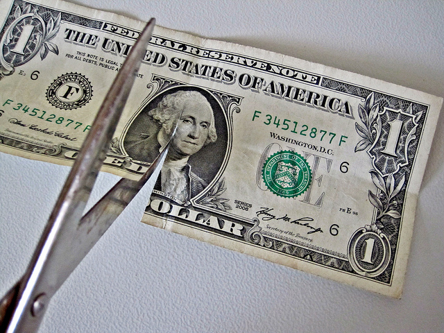 scissors cutting one dollar bill in half