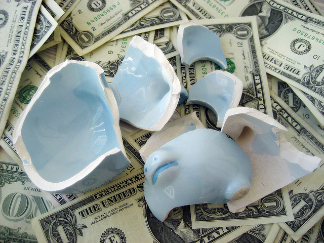 broken piggy bank over pile of one dollar bills